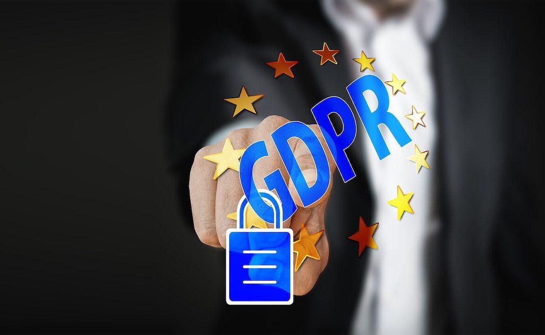 Dito che indica scritta GDPR dentro bandiera dell'Unione Europea