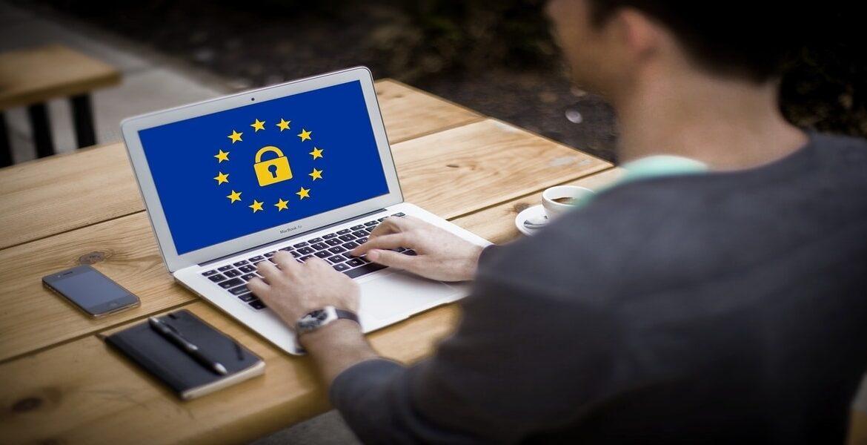 Immagine con persona che scrive al computer con bandiera unione europea nello schermo