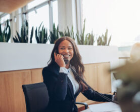 smiling-african-american-businesswoman-talking-on-XHFN6FA-scaled-555x370