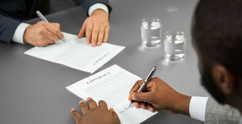 Immagine con due persone che firmano contratti