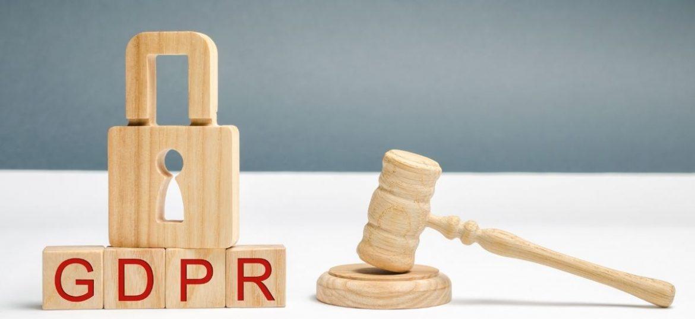 Scritta GDPR con lucchetto, simbolo della privacy e martelletto da giudice che dà una sanzione
