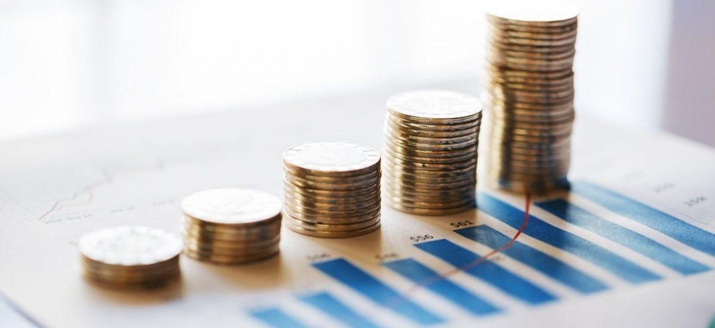 Pile di monete ordinate a scala su un foglio che riporta dati